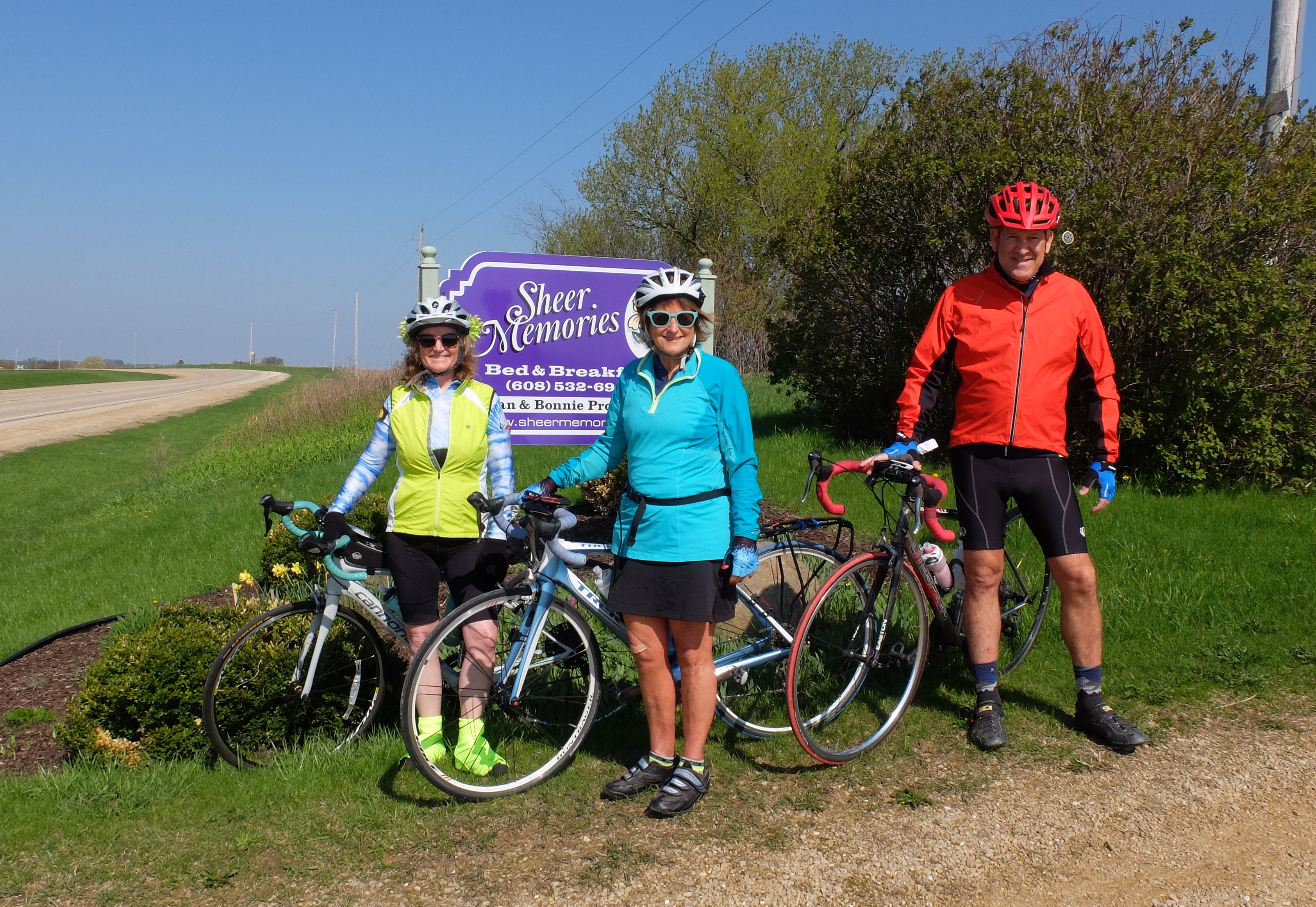 Three bikers in front of Sheer Memories B&B sign ready for trails